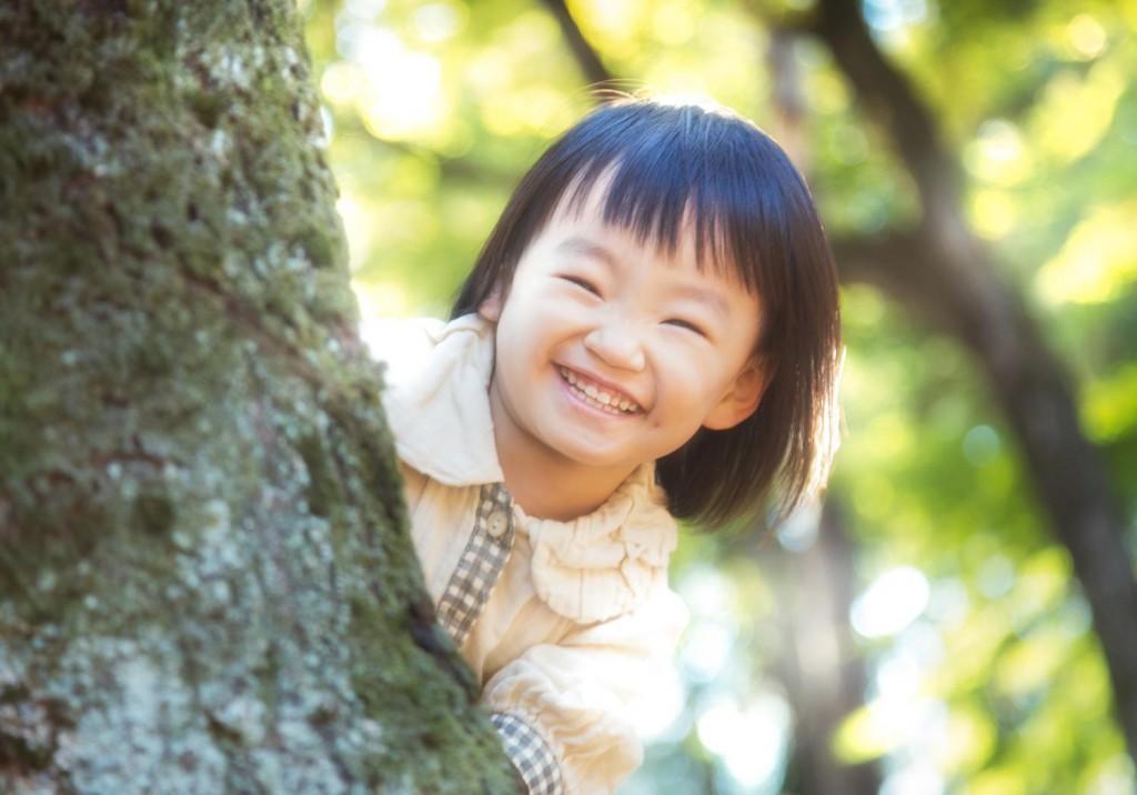 木の陰から女の子(笑顔)